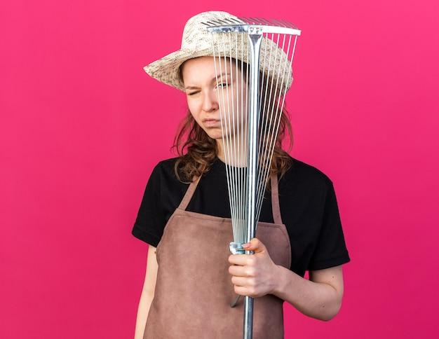 Zelfverzekerde knipperde jonge vrouwelijke tuinman met een tuinhoed met bladhark