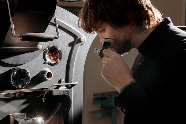 Zelfverzekerde koffiebrander man controleert bereidingsproces