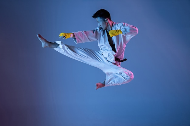 Zelfverzekerde koreaanse man in kimono beoefenen van handtohand gevechtsvechtsporten