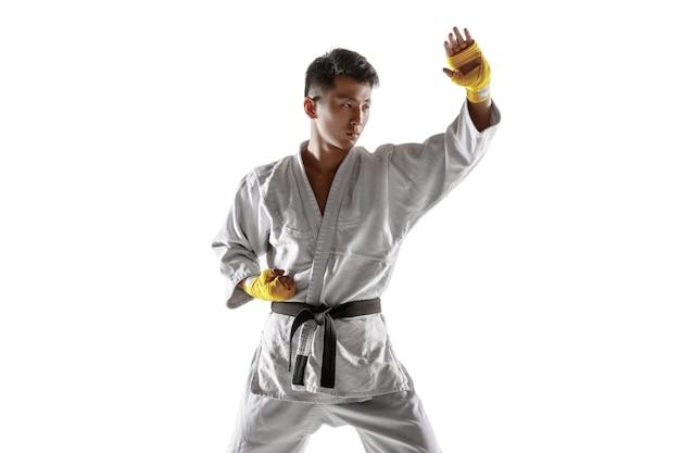 Zelfverzekerde koreaanse man in kimono die hand-tot-hand gevechten beoefent, vechtsporten. jonge mannelijke vechter met zwarte band opleiding geïsoleerd op een witte muur. concept van gezonde levensstijl, sport. Gratis Foto