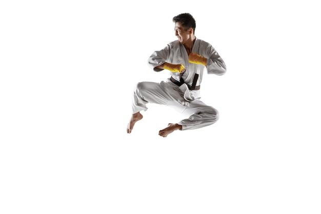 Zelfverzekerde koreaanse man in kimono die hand-tot-hand gevechten beoefent, vechtsporten. jonge mannelijke vechter met zwarte band opleiding geïsoleerd op een witte muur. concept van gezonde levensstijl, sport.