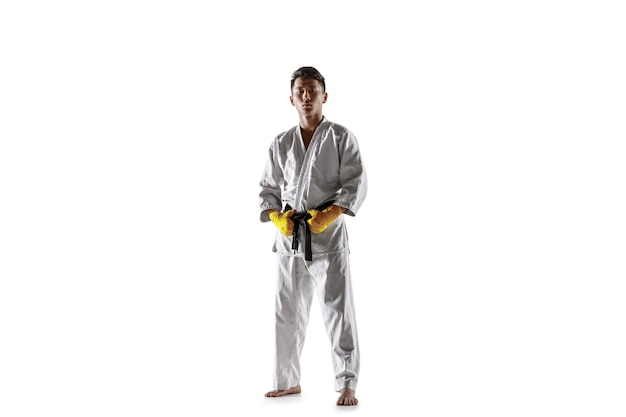 Zelfverzekerde koreaanse man in kimono die hand-tot-hand gevechten beoefent, vechtsporten. jonge mannelijke vechter met zwarte band opleiding geïsoleerd op een witte studio achtergrond. concept van gezonde levensstijl, sport.