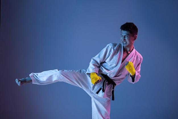 Zelfverzekerde koreaanse man in kimono die hand-tot-hand-gevechten, vechtsporten beoefent.