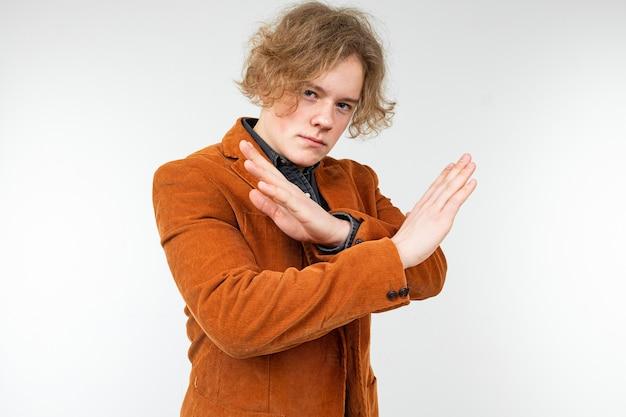 Zelfverzekerde krullende blonde man in een bruin jasje zwaait met zijn handen weg op een witte studioachtergrond.