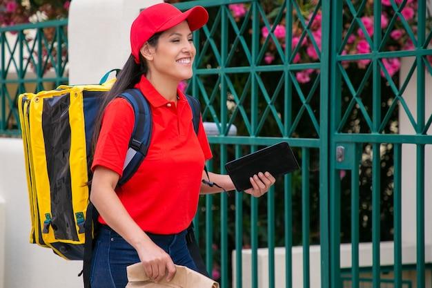 Zelfverzekerde latijnse koerier loopt, bezorgt bestelling, glimlacht en werkt aan de post. jonge bezorger die spijkerbroek, rood uniform draagt en gele thermische rugzak draagt. bezorgservice en postconcept