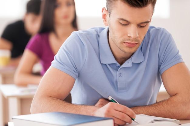 Zelfverzekerde leerling. knappe mannelijke student die iets in notitieblok schrijft terwijl hij in de klas zit met andere studenten