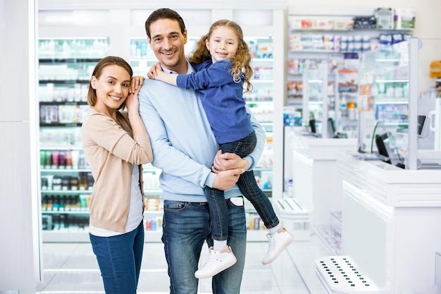 Zelfverzekerde liefdevolle familie komt in drogisterij en camera kijken