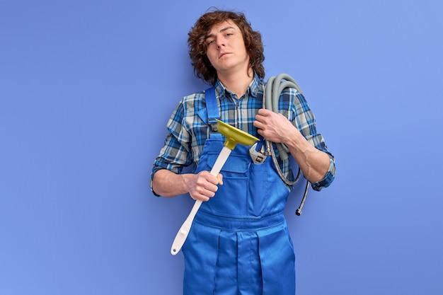 Zelfverzekerde loodgieter man met krullend haar in uniform houden toilet plunjer geïsoleerd op blauwe studio achtergrond