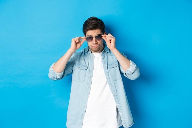 Zelfverzekerde macho man zette een zonnebril op, zag er cool en brutaal uit, staande over een blauwe achtergrond