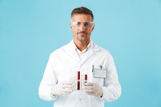 Zelfverzekerde man arts uniform en bril dragen staande geïsoleerd over blauwe muur, bekers houden