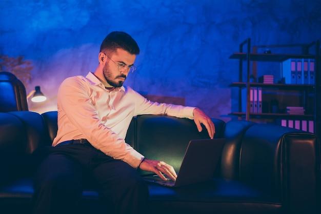 Zelfverzekerde man browsen door zijn laptop nachtkantoor