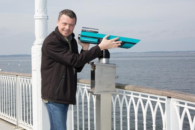 Zelfverzekerde man die dicht bij oceaan toeristische kijken door een verrekijker of telescoop