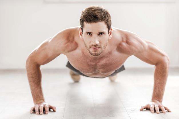 Zelfverzekerde man doet push-ups. zelfverzekerde jonge gespierde man die push-ups doet en naar de camera kijkt
