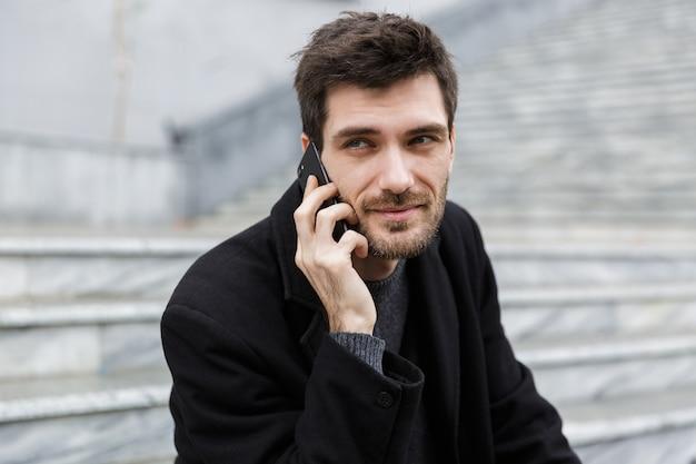Zelfverzekerde man gekleed in jas zittend aan de straat van de stad, praten over de mobiele telefoon