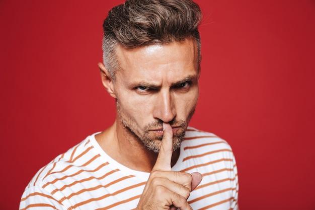 Zelfverzekerde man in gestreept t-shirt met wijsvinger op lippen met strikte blik geïsoleerd op rood