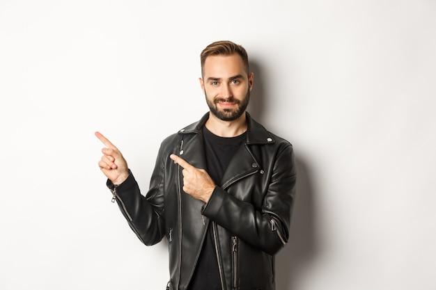 Zelfverzekerde man in zwart leren jasje, wijzende vingers naar links op promo-aanbieding