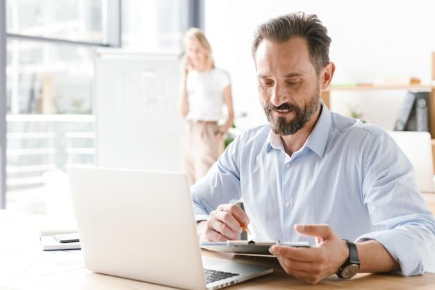 Zelfverzekerde man manager die op laptopcomputer werkt