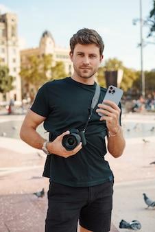Zelfverzekerde man met camera en smartphone die op het stadsplein staat