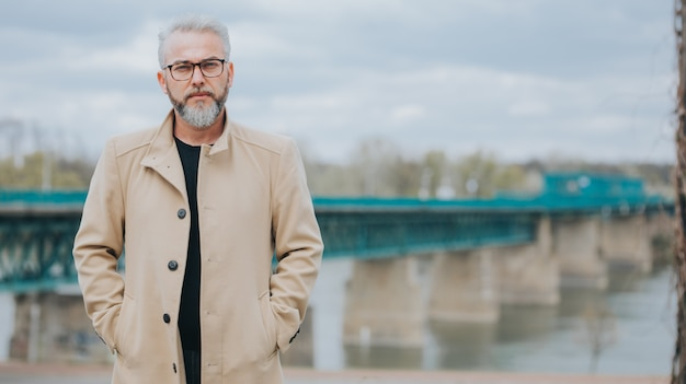 Zelfverzekerde man met grijs haar in een stijlvolle bruine jas met een brug erachter