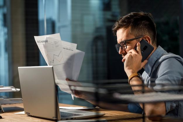 Zelfverzekerde man met papieren spreken op telefoon
