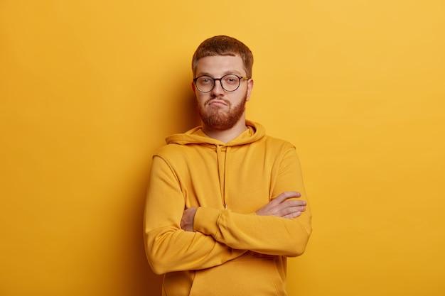Zelfverzekerde man met rood haar en stoppels, kruist armen over de borst, zelfverzekerd en trots op zijn prestaties, nonchalant gekleed, poseert in het geel, vertrouwt het uiterlijk van een vriend niet