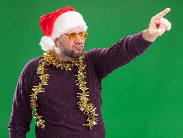 Zelfverzekerde man van middelbare leeftijd met kerstmuts en klatergoud slinger rond nek met bril kijken en wijzend naar kant geïsoleerd op groene achtergrond