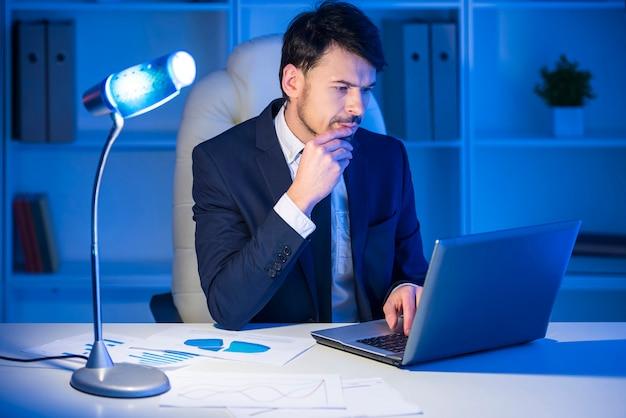 Zelfverzekerde man werkt op laptop in office.