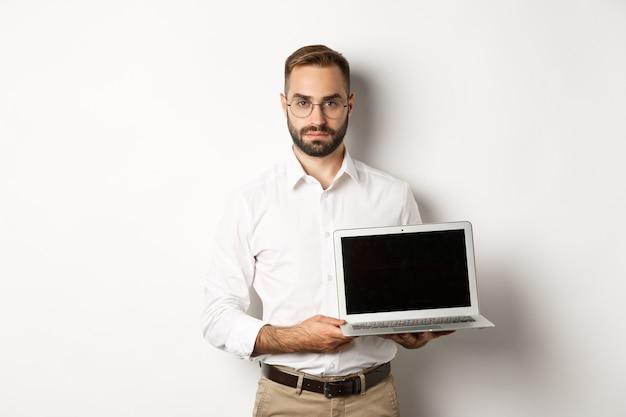Zelfverzekerde manager die presentatie op het scherm demonstreert, laptopscherm toont en er serieus uitziet, staande op een witte achtergrond.