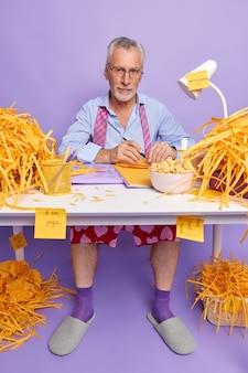 Zelfverzekerde mannelijke directeur werkt vanuit huis tijdens de pandemie van het coronavirus maakt aantekeningen op een rommelige desktop en ontbijt poses op kantoor tegen paarse muur