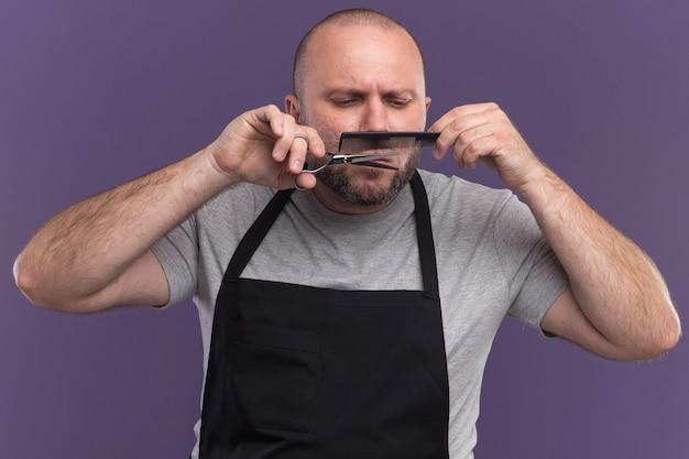 Zelfverzekerde mannelijke kapper van middelbare leeftijd in uniform trimmen snor met schaar geïsoleerd op paarse muur