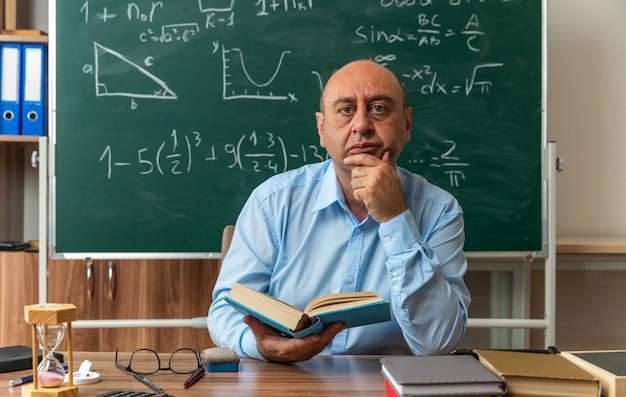 Zelfverzekerde mannelijke leraar van middelbare leeftijd zit aan tafel met schoolbenodigdheden en houdt een boek vast en pakt de kin in de klas