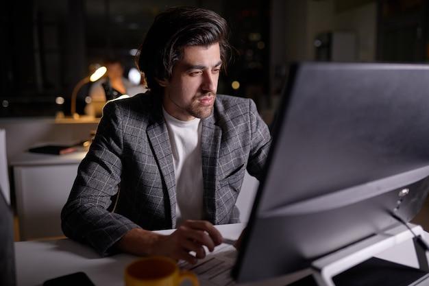 Zelfverzekerde mannelijke programmeur die 's nachts op de computer werkt. tafellamp aan. blanke man in formele slijtage bezig met werk, in kantoor in donker kantoor. netwerken, freelancen, deadline. ruimte kopiëren