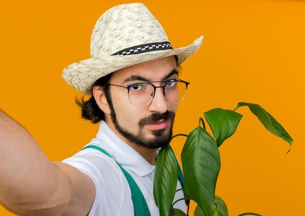 Zelfverzekerde mannelijke tuinman in optische bril tuinieren hoed houdt plant en beweert camera vast te houden