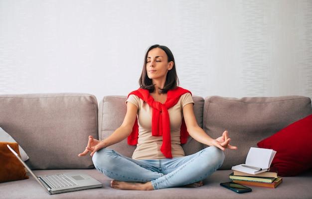 Zelfverzekerde moderne schattige jonge vrouw is online werken en ontspannen thuis op de bank met haar laptop op de freelance baan