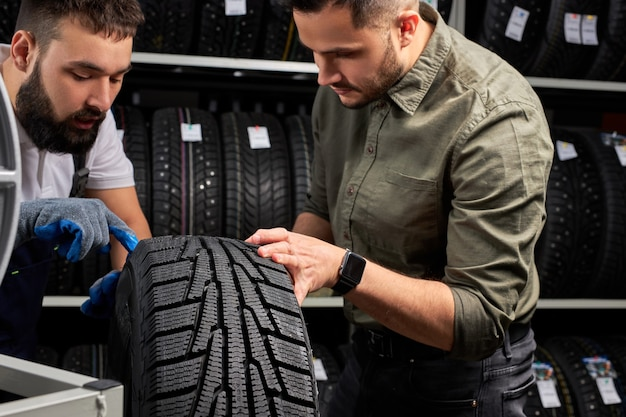 Zelfverzekerde monteur en klant banden in winkel controleren, gesprek in winkel, klant gaat kopen. zachte focus