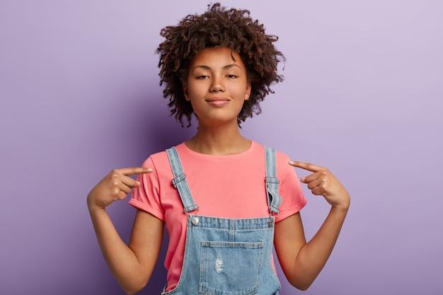 Zelfverzekerde mooie afro-amerikaanse vrouw voelt zich trots op haar daden, wijst naar zichzelf, voelt een golf van trots, heft het hoofd op, heeft een donkere, gezonde huid, draagt vrijetijdskleding, geïsoleerd over paarse muur