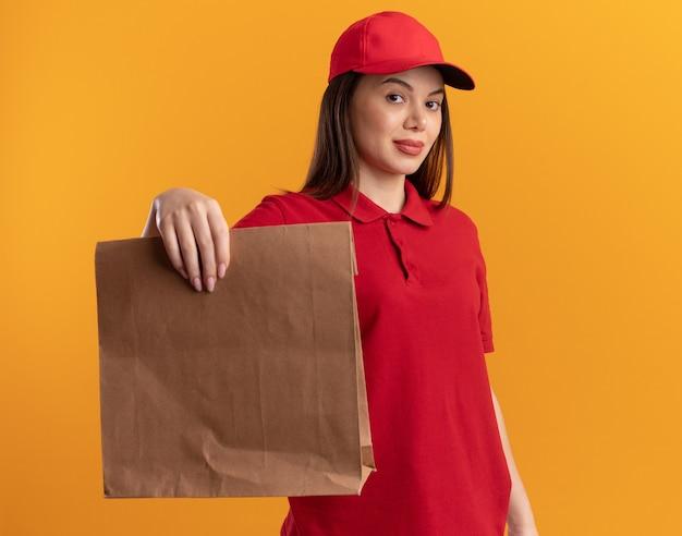 Zelfverzekerde mooie bezorger in uniform houdt papieren pakket vast
