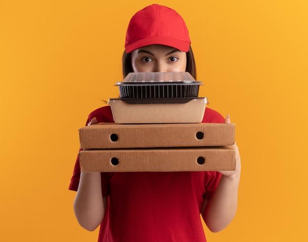 Zelfverzekerde mooie bezorger in uniform houdt papieren voedselpakketten op pizzadozen op oranje