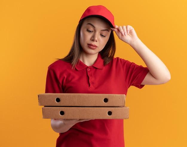 Zelfverzekerde mooie bezorger in uniform legt hand op glb houden en kijken naar pizzadozen op oranje