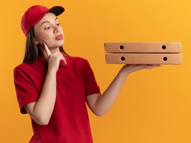 Zelfverzekerde mooie bezorger in uniform legt vinger op gezicht en kijkt naar pizzadozen op oranje