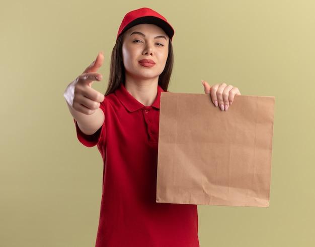 Zelfverzekerde mooie bezorgvrouw in uniform houdt papieren pakket vast en wijst op camera op olijfgroen