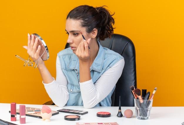 Zelfverzekerde, mooie blanke vrouw die aan tafel zit met make-uphulpmiddelen die naar een spiegel kijken die oogschaduw toepast
