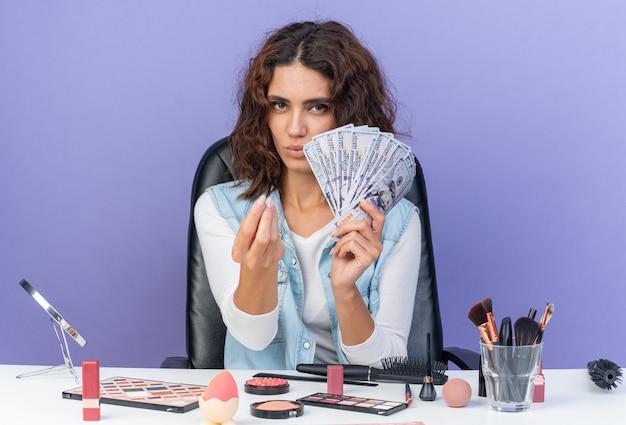 Zelfverzekerde mooie blanke vrouw die aan tafel zit met make-uptools die geld aanhouden