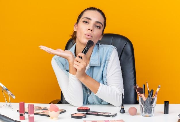Zelfverzekerde, mooie blanke vrouw die aan tafel zit met make-uptools die make-upborstel vasthoudt en blaast