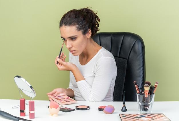 Zelfverzekerde, mooie blanke vrouw die aan tafel zit met make-uptools die oogschaduw aanbrengen met een make-upborstel die naar de spiegel kijkt en een oogschaduwpalet vasthoudt