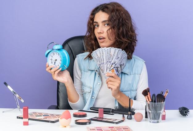 Zelfverzekerde, mooie blanke vrouw die aan tafel zit met make-uptools met geld en wekker