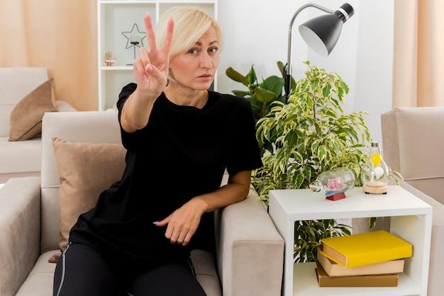 Zelfverzekerde mooie blonde russische vrouw zit op fauteuil gebaren overwinning handteken in de woonkamer