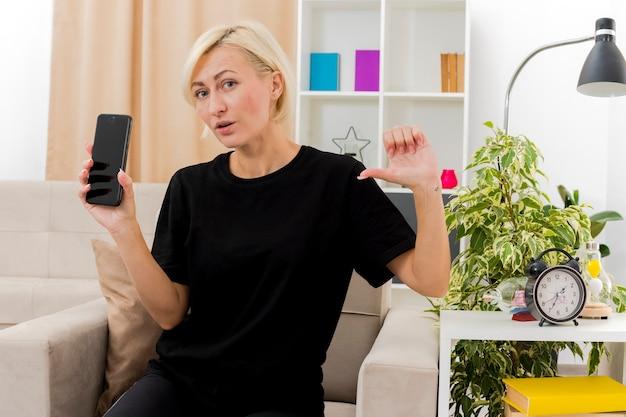 Zelfverzekerde mooie blonde russische vrouw zit op fauteuil houden en wijzen op de telefoon