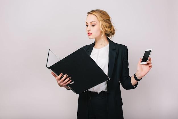 Zelfverzekerde mooie blonde zakenvrouw in kantoor pak kijken naar map in handen, telefoon bedrijf. druk bezig zijn, werker, secretaris, manager, succesvol