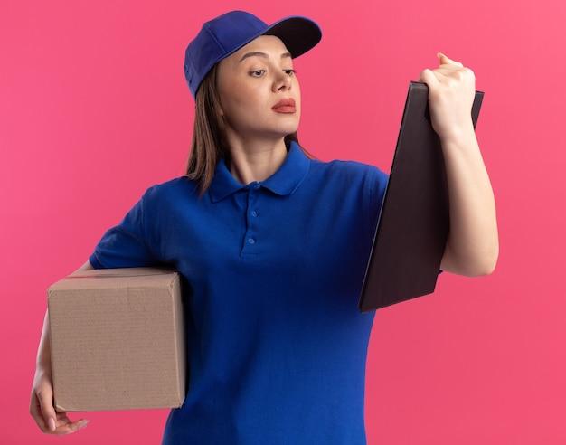 Zelfverzekerde mooie levering vrouw in uniform houdt kartonnen doos en kijkt naar klembord op roze